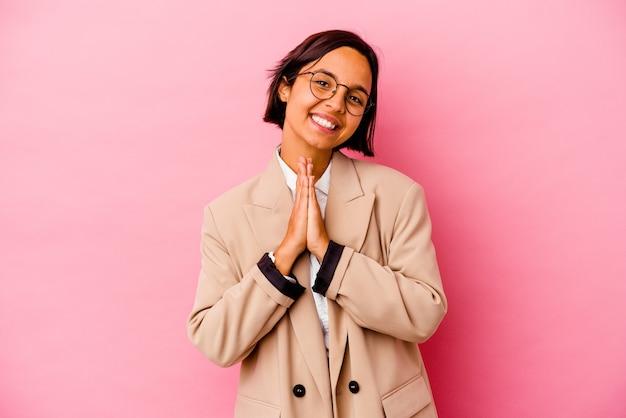 Femme de race mixte jeune entreprise isolée sur un mur rose tenant par la main en priant près de la bouche, se sent confiant.
