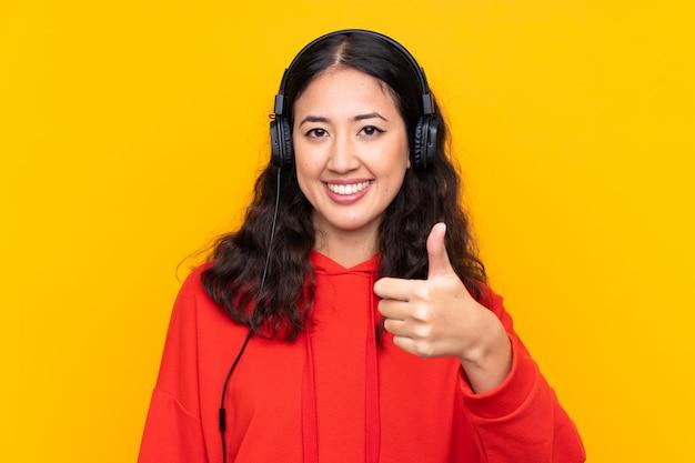 Femme de race mixte portant un sweat-shirt rouge écoutant de la musique et avec le pouce