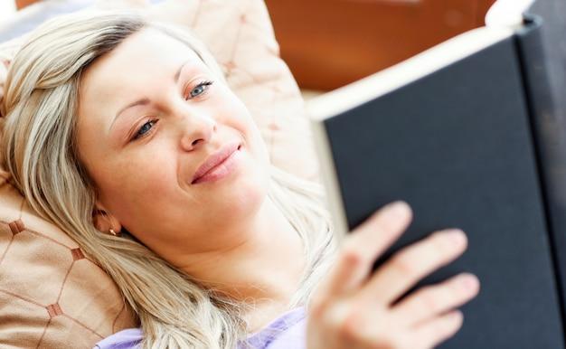 Femme radieuse allongée sur un canapé et lisant un livre