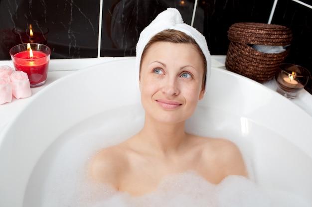 Femme radieuse relaxante dans un bain moussant