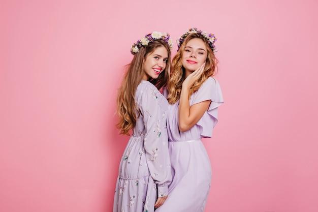 Femme raffinée aux cheveux ondulés blonds posant avec soeur sur mur rose
