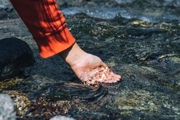 Femme ramassant de l'eau de la vallée