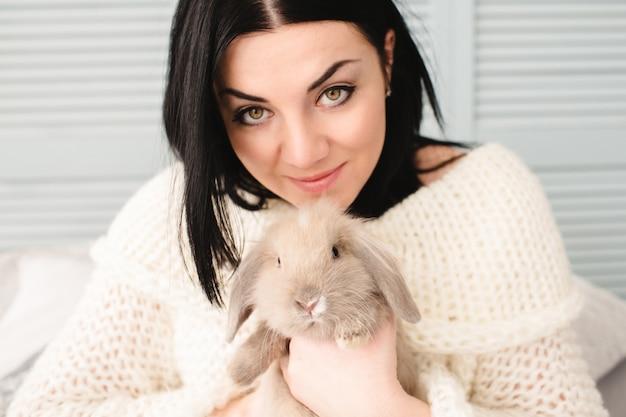 Femme ramassant un lapin gris