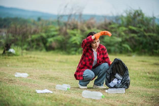 Femme ramassant des ordures dans un sac noir.
