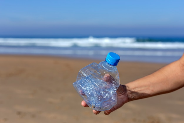 Femme ramassant des ordures et des plastiques nettoyant la plage
