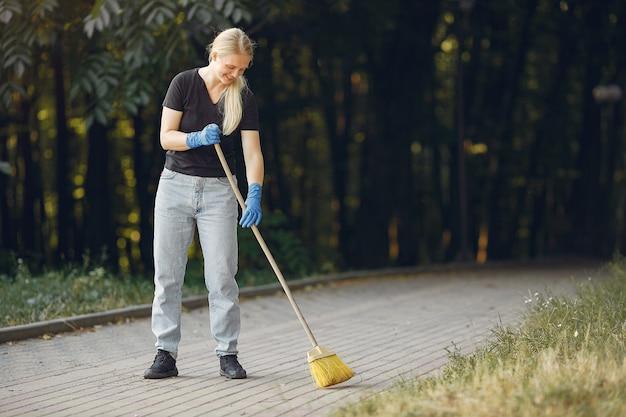 Femme ramasse des feuilles et nettoie le parc