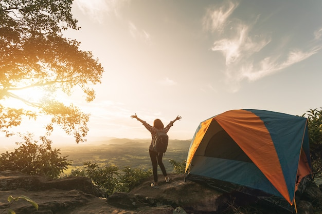 Femme de randonneur asiatique debout près de tente de camping dans les carpates. touriste profiter de la montagne