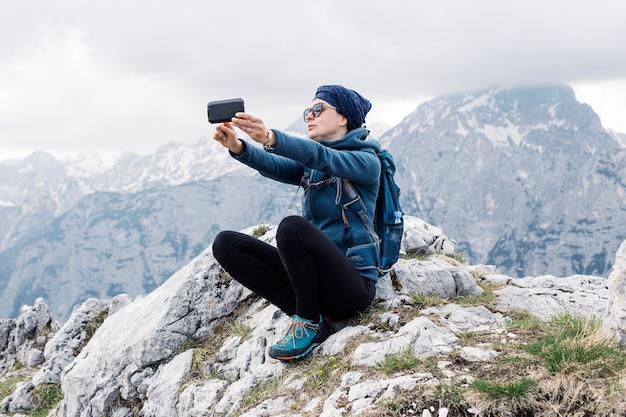 Femme randonneur faisant un selfie avec son téléphone intelligent avec des collines en arrière-plan