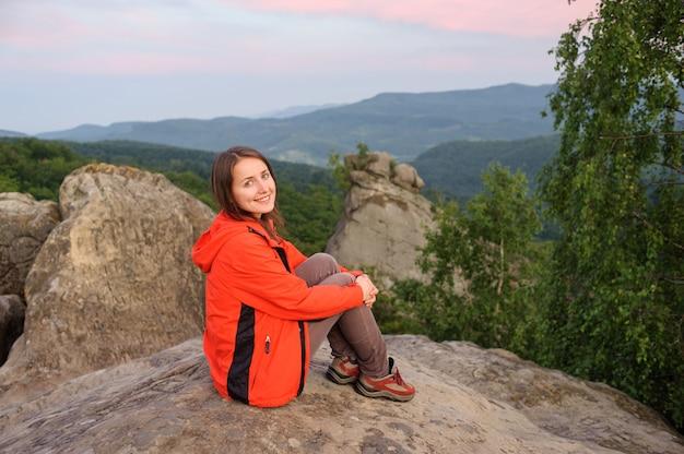 Femme randonneur sur le gros rocher au sommet de la montagne