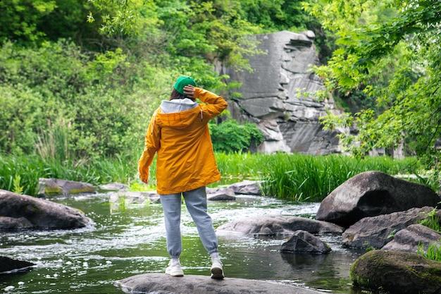 Femme de randonneur en imperméable jaune, profitant de la vue sur la rivière dans la beauté du canyon dans la nature