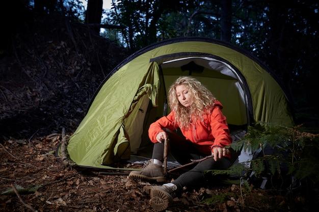 Femme randonneur avec tente dans la forêt