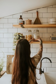 Femme rangeant le garde-manger mural de la cuisine
