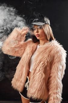 Femme rap à la mode en manteau de fourrure rose et caping sur noir