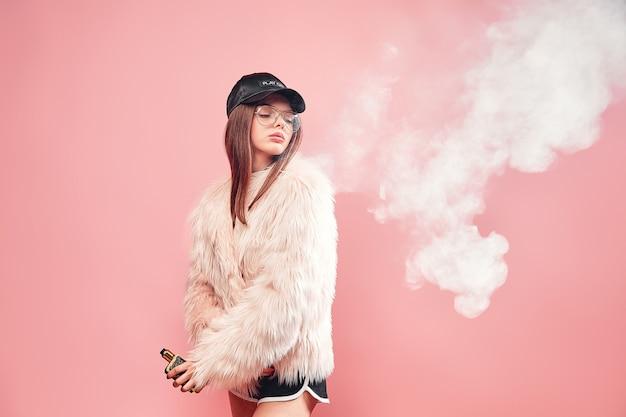 Femme rap sexy à la mode en manteau de fourrure rose et casquette fumant une cigarette électronique sur rose