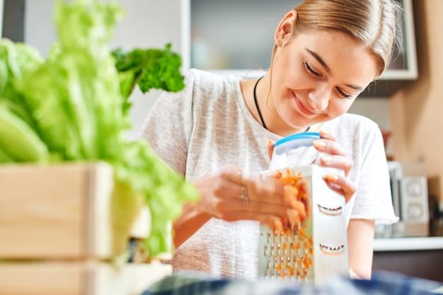Femme râpe les carottes dans la cuisine