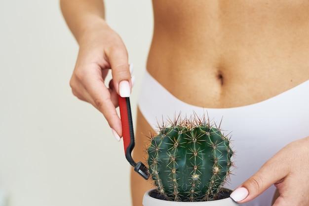 Une femme rase un cactus avec un rasoir contre le mur de sa culotte.