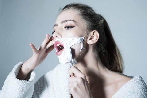Femme rase son visage avec une lame tranchante de rasoir droit femme avec le visage recouvert de mousse tient un rasoir droit dans la main fille sur le visage occupé porte un peignoir gris