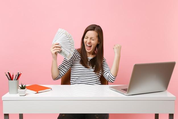 Une femme ravie criant les poings serrés comme un gagnant tenant un paquet de dollars, de l'argent en espèces travaille au bureau blanc avec un ordinateur portable