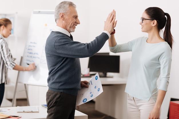 Femme ravie portant des lunettes touchant les mains avec son partenaire en position semi