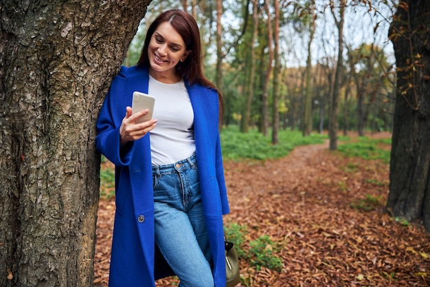 Femme ravie positive regardant l'écran de son gadget