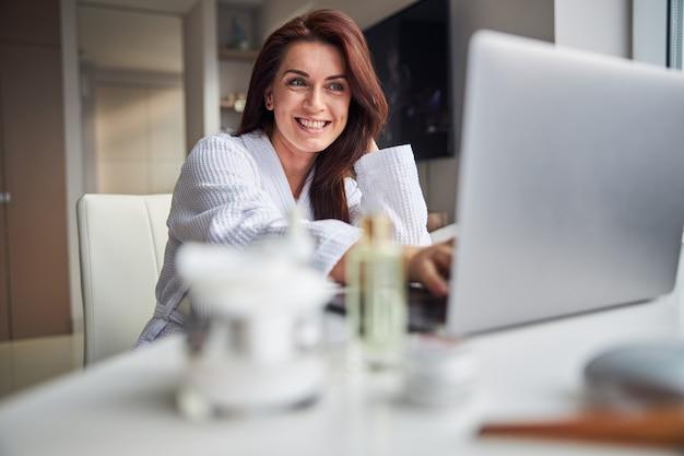 Femme ravie positive regardant son ordinateur portable