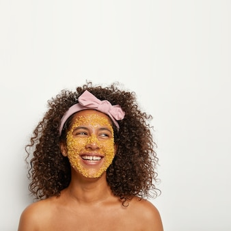 Une femme ravie positive rit joyeusement, a une procédure de beauté, applique un gommage aux granules jaunes pour un effet anti-âge, renouvelle les cellules, a une peau radieuse, porte un bandeau avec un arc sur la tête, se tient torse nu