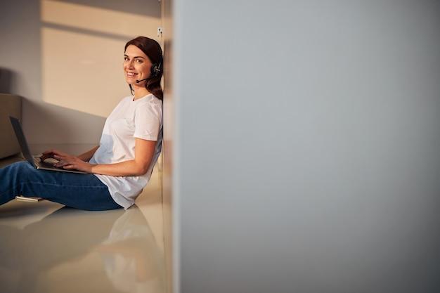 Femme ravie positive travaillant à distance