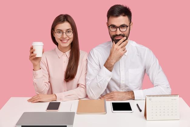 Une femme ravie a un sourire à pleines dents, porte des lunettes optiques, tient un café à emporter, a une expression heureuse