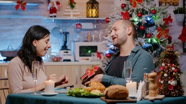 Femme recevant un cadeau de son mari lors d'un dîner de fête