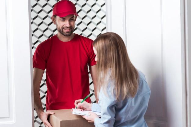 Femme recevant un colis du courrier par-dessus l'épaule