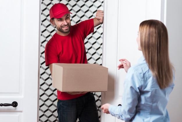 Femme recevant un colis du courrier