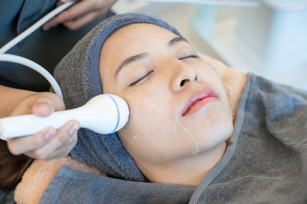 Femme recevant des cosmétiques anti-âge à l'aide d'une machine de cavitation à ultrasons.