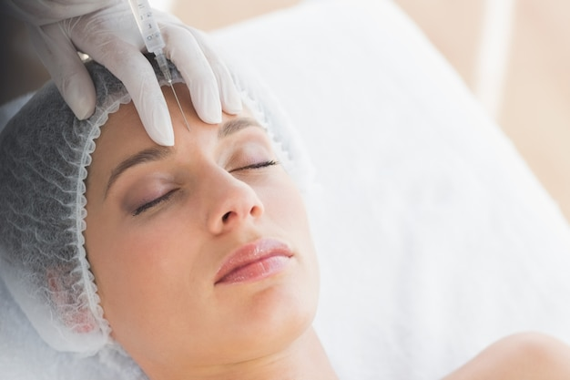 Femme recevant l'injection de botox dans le front