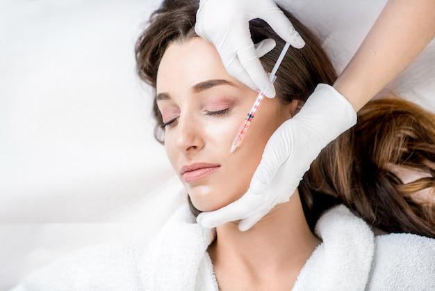 Femme recevant une injection de botox dans la zone des lèvres allongée en peignoir sur le canapé médical