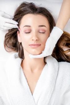 Femme recevant une injection de botox dans la zone des yeux allongée en peignoir sur le canapé médical
