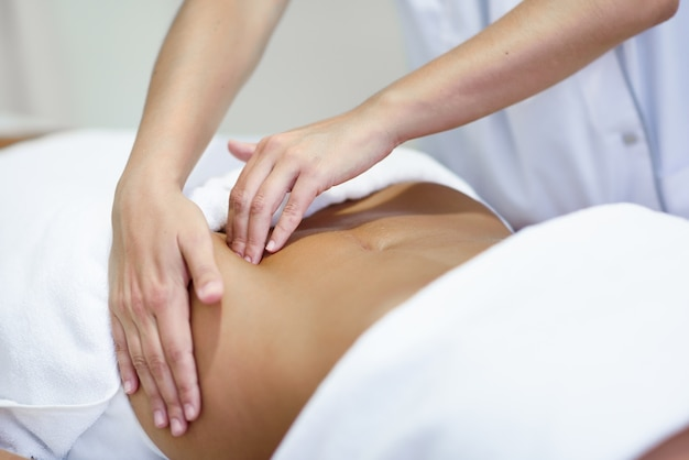 Femme recevant un massage du ventre au salon de spa