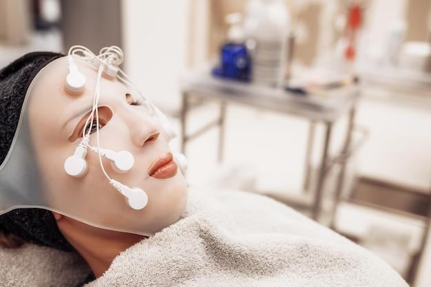 Femme recevant un massage du visage dans un salon de beauté.
