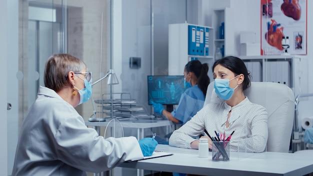 Femme recevant de mauvaises nouvelles chez le médecin en période de covid-19, pleurant, portant un masque de protection, parlant à travers un mur en plexiglas. consultation médicale dans le concept d'équipement de protection shot de sars-cov-2 glo