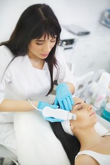 Femme recevant un peeling facial électrique au salon de beauté européen.