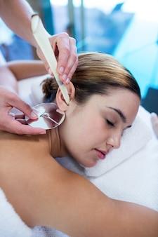 Femme recevant un traitement de bougie d'oreille