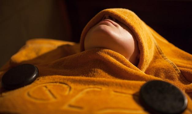 Femme recevant un traitement de serviette chaude au spa de beauté