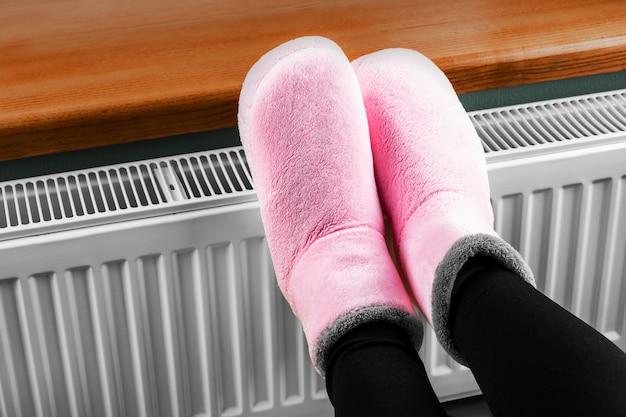 Femme réchauffe ses mains sur le radiateur