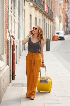 Femme à la recherche d'un appartement portant une valise dans la ville