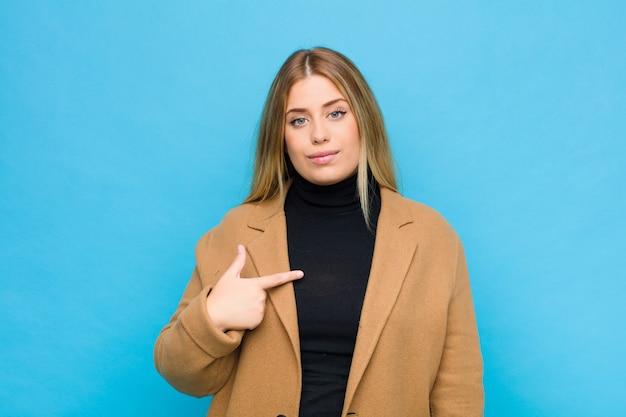 Femme à la recherche de fierté, confiant et heureux, souriant et pointant vers soi ou faisant signe numéro un