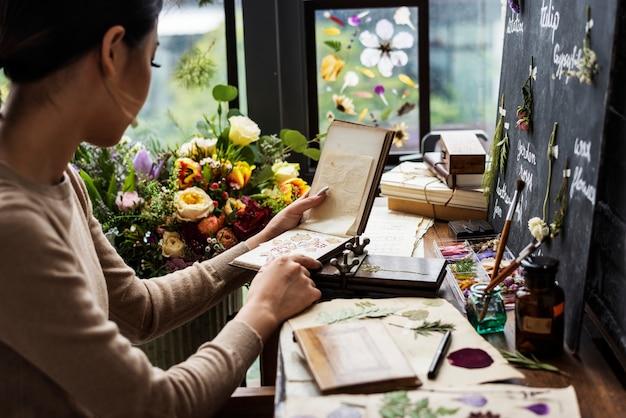 Femme à la recherche d'un livre de fleurs séchées