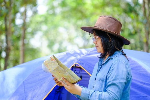 Femme à la recherche d'une route avec carte et horloge dans la forêt