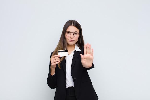 Femme à la recherche de sérieux, sévère, mécontent et en colère montrant la paume ouverte faisant un geste d'arrêt