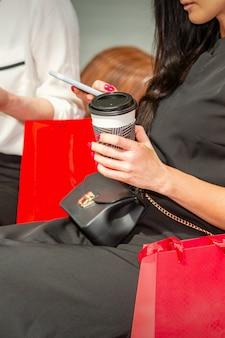 Femme à la recherche de smartphone dans le centre commercial