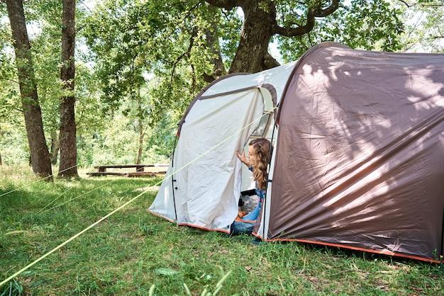 Femme à la recherche de tente touristique sur matin ensoleillé en forêt