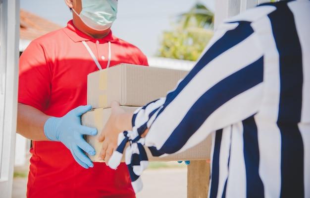 La femme reçoit une boîte à colis du personnel de livraison.